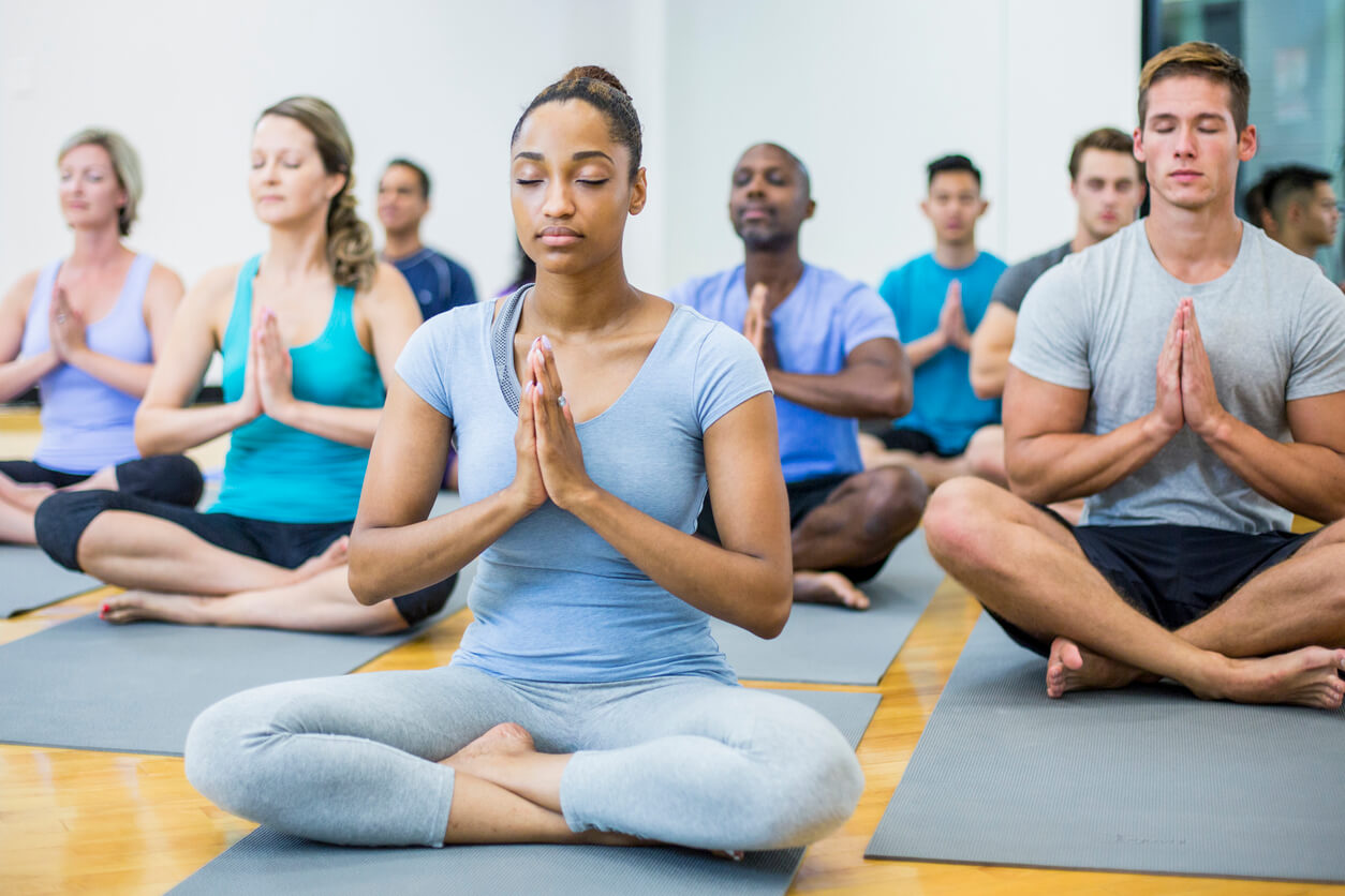 A multi-ethnic group of adults are indoors in a fitness center. They are wearing exercise clothes and shoes. Here they are doing meditation with their eyes closed.